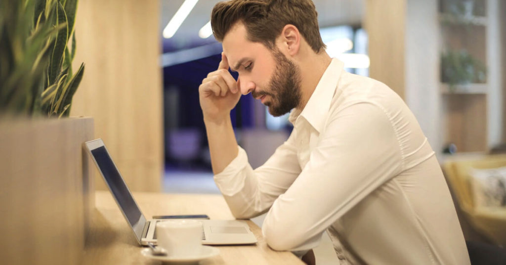 Man looking at laptop thinking